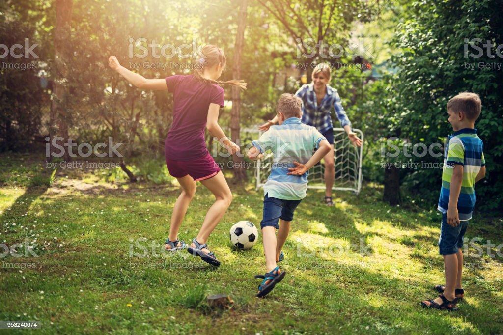 Family having fun playing soccer in the garden stock photo