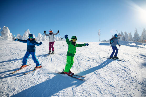 Family having fun skiing together on winter day Mother with kids are skiing together down the ski slope. Everybody is laughing happily.  Sunny winter day. Nikon D850 ski stock pictures, royalty-free photos & images