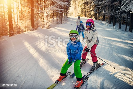 Mother with kids are skiing together down the ski slope. Everybody is laughing happily.