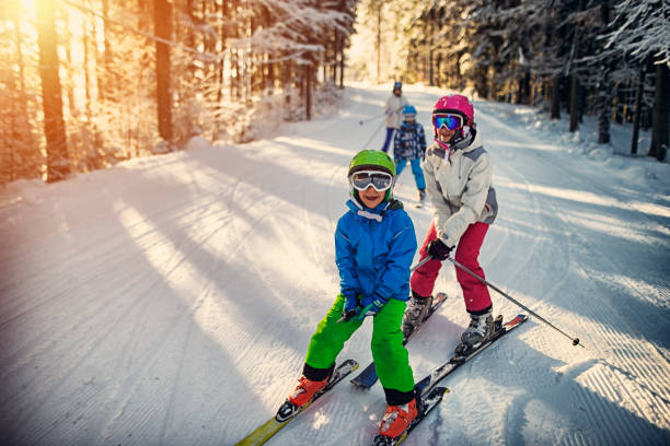 Family having fun skiing together on winter day Mother with kids are skiing together down the ski slope. Everybody is laughing happily.    ski stock pictures, royalty-free photos & images