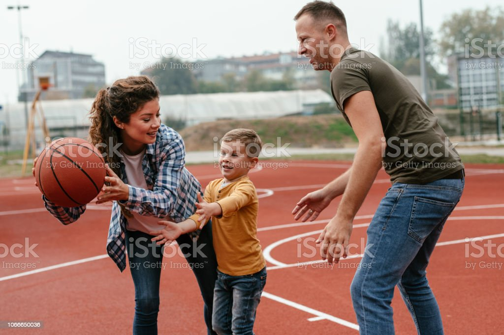 Family having fun time at basketball field. Shallow DOF. Developed...
