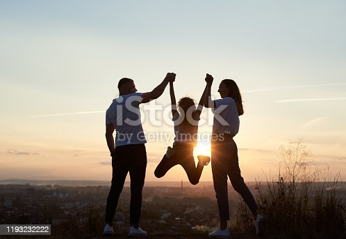 Silhouette of father, mother and daughter having fun outside the city on the hill on the sunset with a beautiful city view, man and woman holding girl by hands and she is jumping, back view