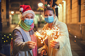 istock Family having fun while celebrating Christmas during COVID-19 pandemic. They wears a protective mask to protect from coronavirus COVID-19. 1273207450