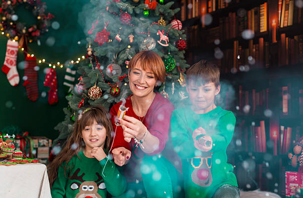 family having fun with christmas petards - petard stock photos and pictures