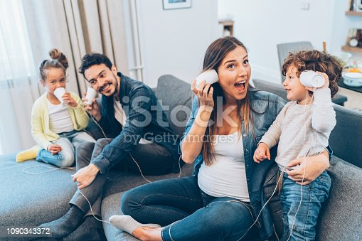 Family having fun playing with string phones at home