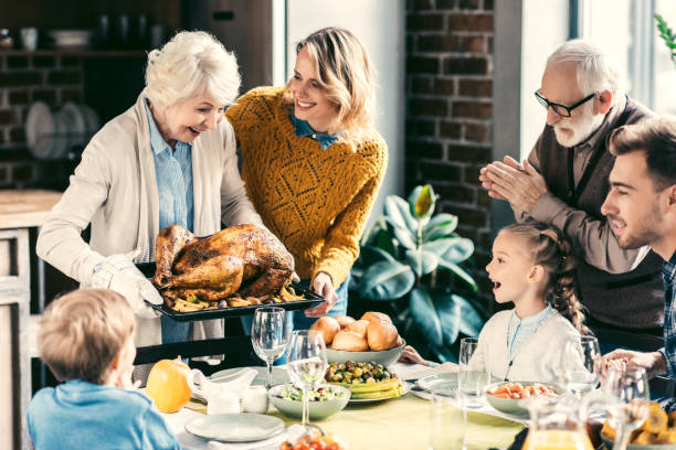 family having holiday dinner - thanksgiving stock photos and pictures