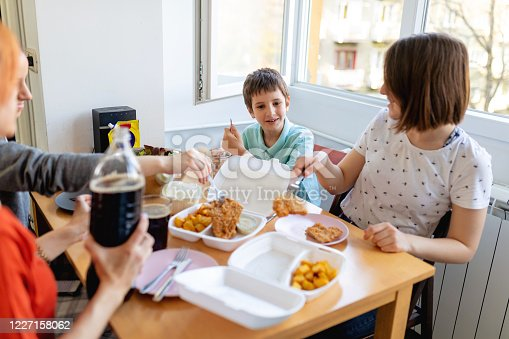 Mid adult woman ordered a take out food from delivery and putting it on dining table to have lunch with family at home during stay at home order