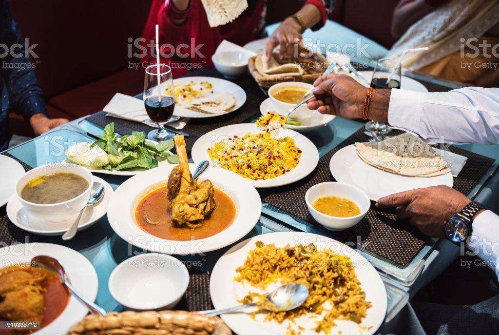 Familia que tiene la comida de la India - foto de stock