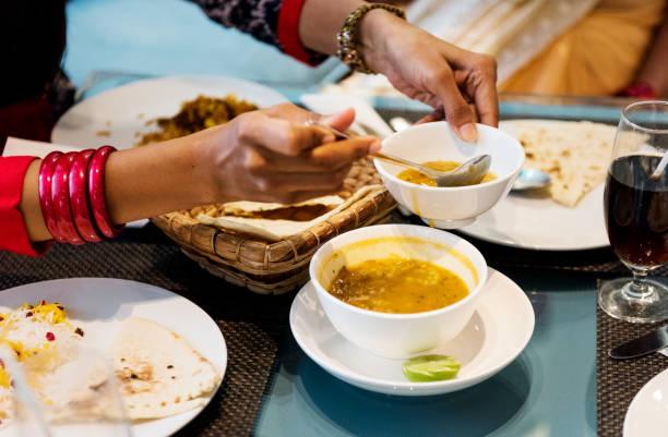 familia que tiene la comida de la india - comida india fotografías e imágenes de stock