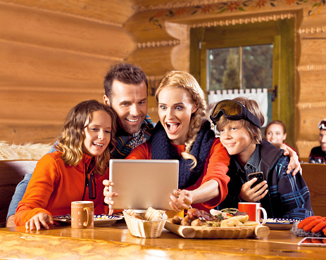 Family Having Lunch After Skiing Using Digital Tablet Stock Photo - Download Image Now