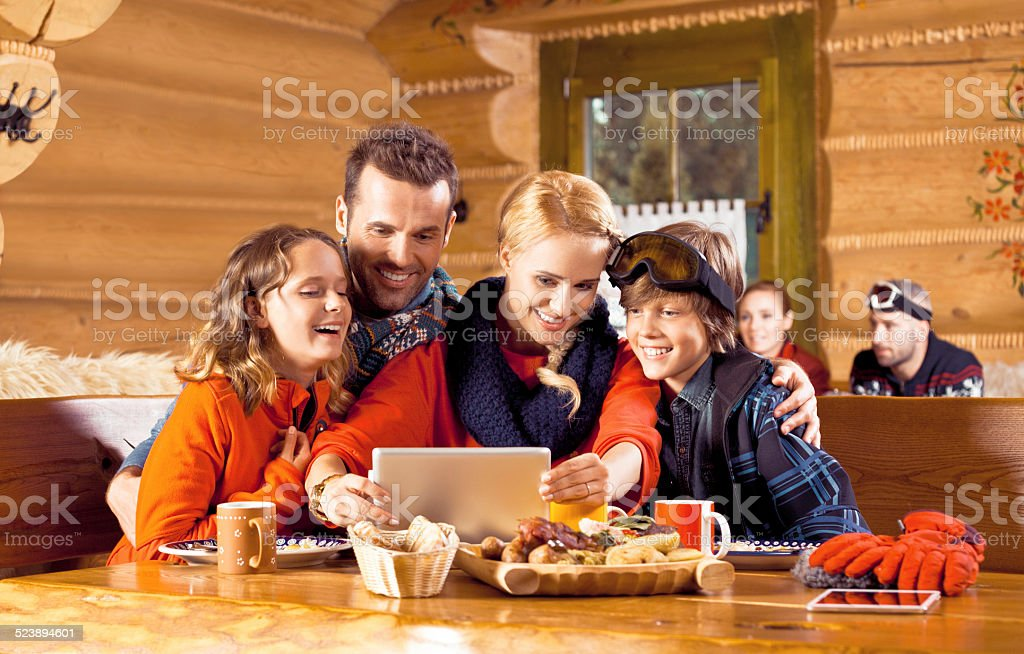 Family having lunch after skiing, using digital tablet Excited Mother, father and their children wearing winter clothes sitting in a mountain restaurant after skiing, having lunch and using a digital tablet. Adolescence Stock Photo
