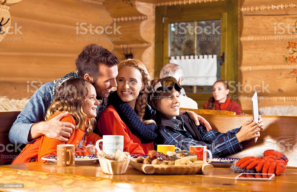 Family having lunch after skiing, using digital tablet Mother, father and their children wearing winter clothes sitting in a mountain restaurant after skiing, having lunch and using a digital tablet. Adolescence Stock Photo