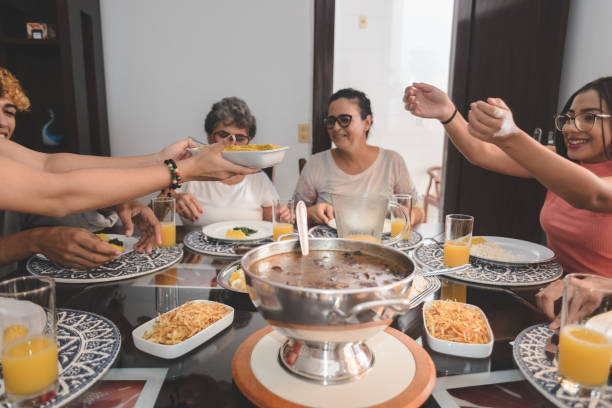 Family having lunch at dining table served with feijoada, typical brazilian black bean stew stock photo