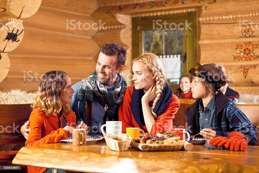 Family having lunch in restaurant after skiing Mother, father and their children wearing winter clothes sitting in a mountain restaurant after skiing, talking and enjoying dinner. Adolescence Stock Photo