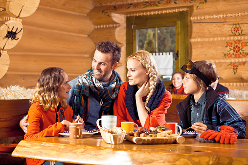 Family Having Lunch In Restaurant After Skiing Stock Photo - Download Image Now