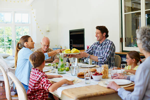 family having meal at dining table - dining table stock photos and pictures