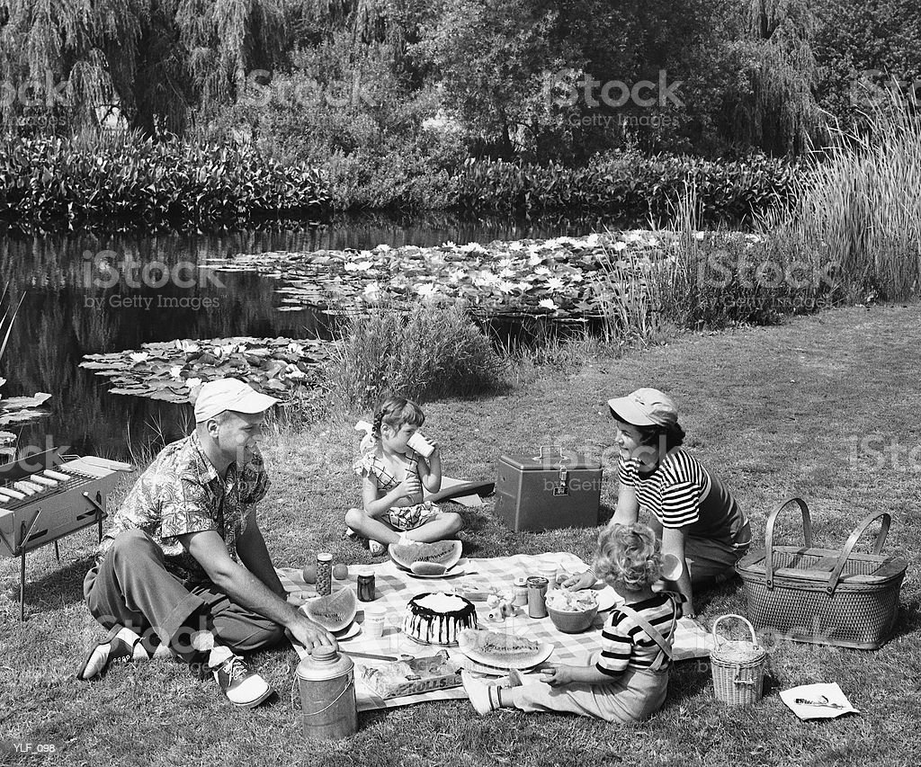 Family having picnic by pond royalty-free stock photo