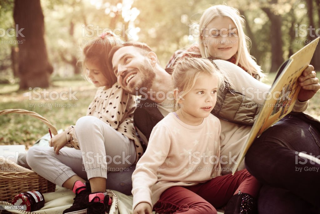 Family having picnic in park. Father holding book to his daughter. royalty-free stock photo