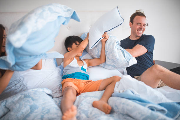 Family having pillow fight in the bed stock photo