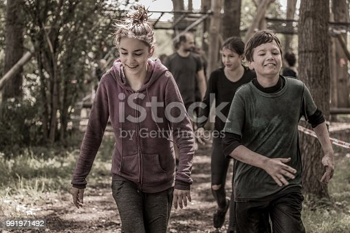 Family having sporty fun at a public mud run obstacle course