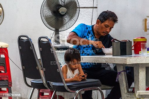 Bangkok, Thailand - April 12, 2019: Father having lunch in a street restaurant and child playing with a mobile phone