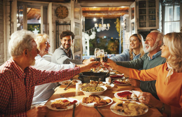 family having thanksgiving dinner. - party social event stock pictures, royalty-free photos & images