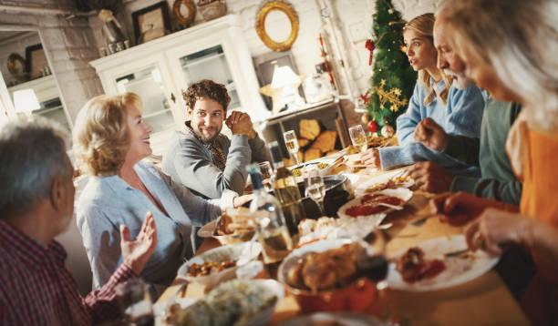 family having thanksgiving dinner. - pranzo di natale foto e immagini stock