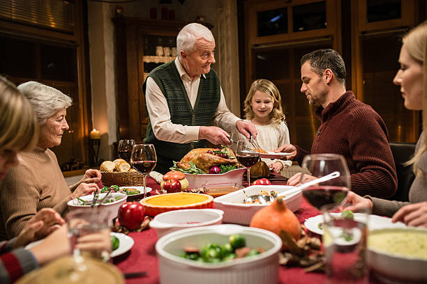 family having thanksgiving dinner - bordsskick bildbanksfoton och bilder