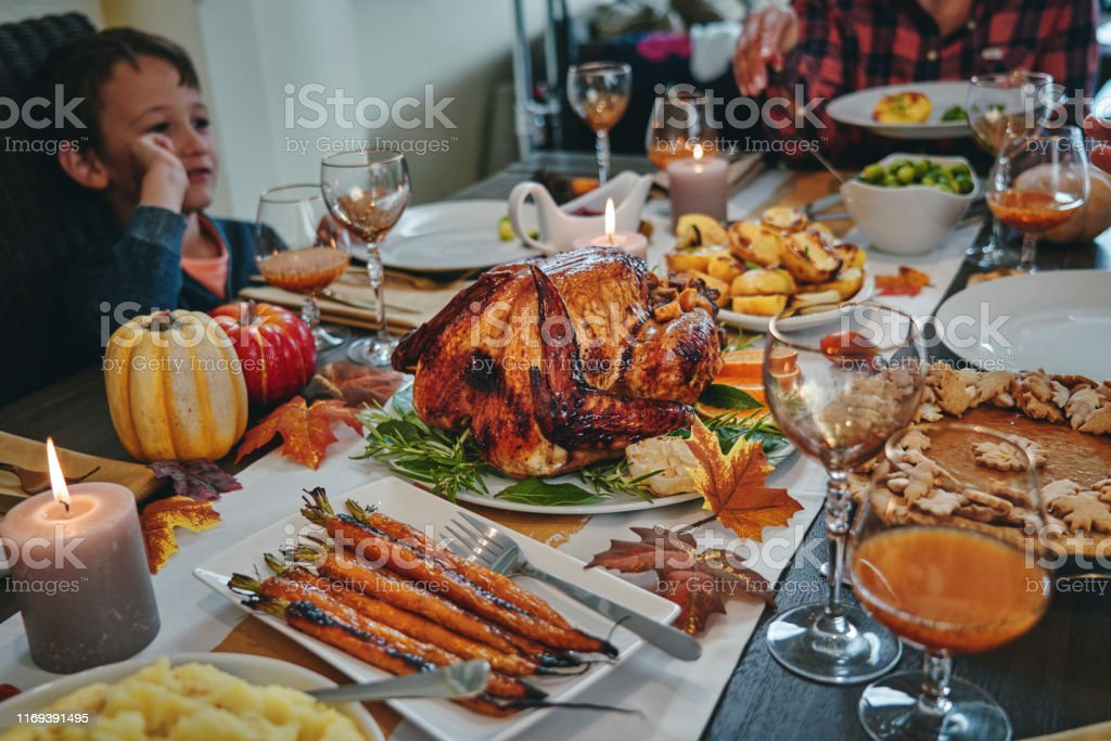 Family Having Traditional Holiday Dinner with Stuffed Turkey, Roasted...