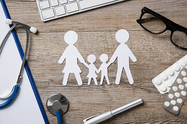 Family healthcare Top view of family paper chain on a doctor desk. Medical worktable with keyboard, blue stethoscope, pills and eyeglasses. Family healthcare, medicine and insurance concept. general practitioner stock pictures, royalty-free photos & images