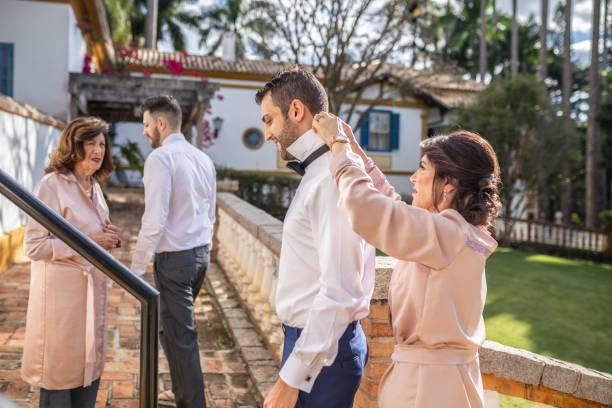 familie hilft bräutigam trägt eine fliege - wie lange leben fliegen stock-fotos und bilder