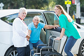A senior man smiling at the camera as he goes from back seat of car into a wheelchair. His wife is holding his hand and his adult daughter is behind the wheelchair, holding the car door open.