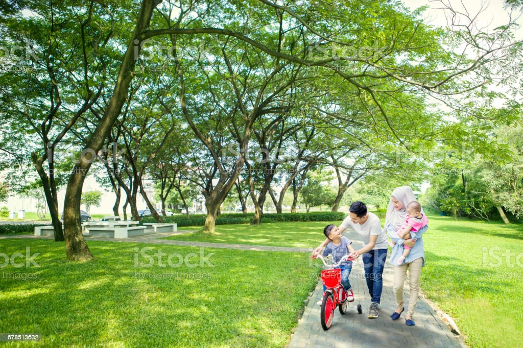 Family helping their son to ride a bike stock photo