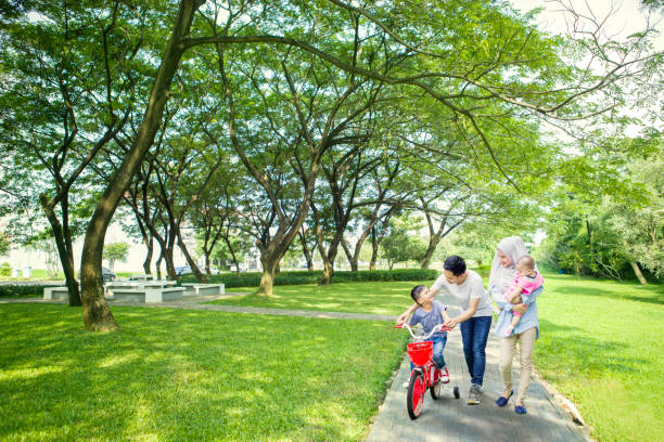 Family helping their son to ride a bike Image of cute boy learns to ride a bike with his family while walking together in the park indonesian ethnicity stock pictures, royalty-free photos & images