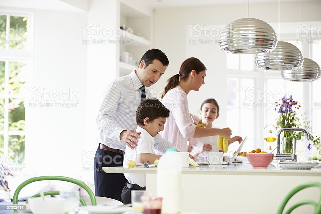 Family Helping To Clear Up After Breakfast stock photo