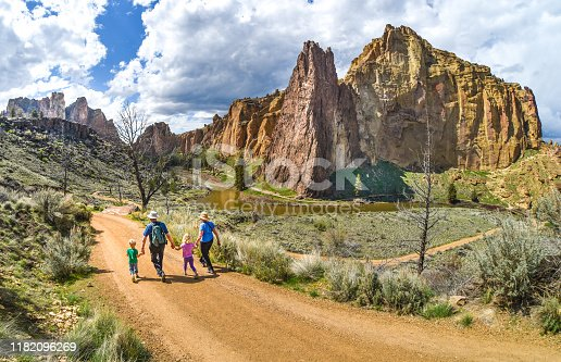 Two children hold hands with their grandparents while hiking at Smith Rock State Park, Oregon.