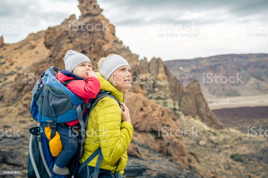 Family hike, mother with baby in backpack stock photo