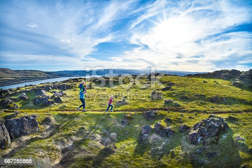 A mother and her two young children hike through a meadow at Horsethief Butte in Columbia Hills State Park, Washington State. Mt. Hood, the Columbia River, and The Dalles, Oregon are in the background.