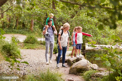 istock Family Hiking Along Path By River In UK Lake District 1049853630