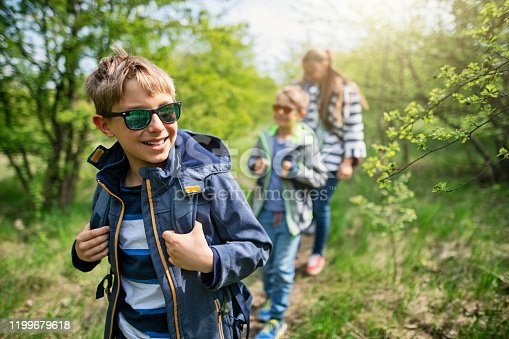 Little boy aged 9 hiking in spring forest with his family.\nNikon D850