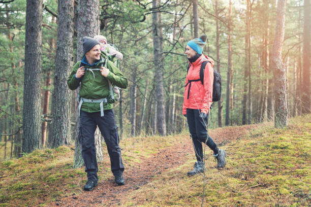 family hiking in the forest with baby in child carrier stock photo