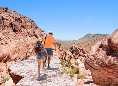 Father and daughter hiking in Red Rock Canyon, Nevada, USA. Girl is wearing a backpack. Blue sky in the background.