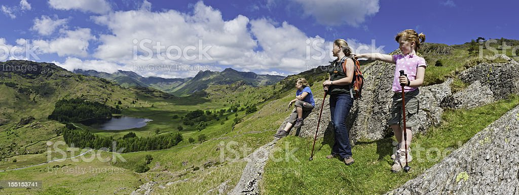 Family hiking looking over idyllic mountain valley stock photo