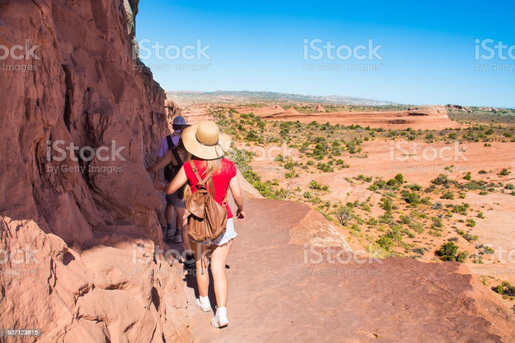 Family hiking on  Delicate Arch trail in Utah. stock photo