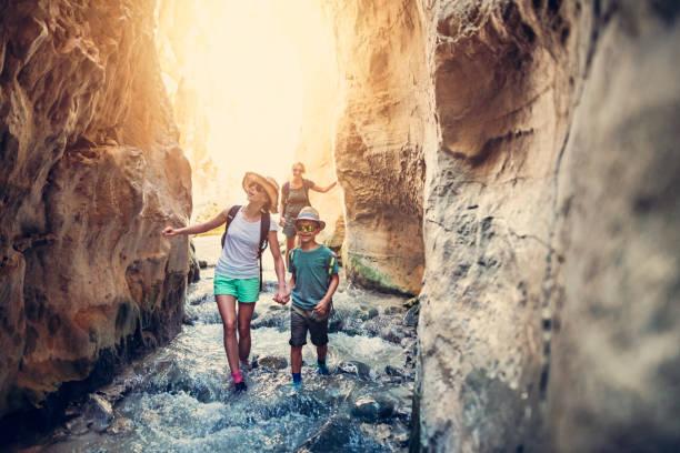 família que caminha através do rio na andaluzia, spain - com os pés na água - fotografias e filmes do acervo