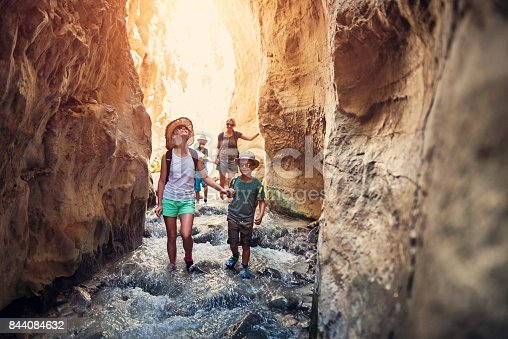 Mother and kids hiking through river Rio Chillar in Andalusia, Spain. They are walking in the mountain river flowing through the narrow canyon.