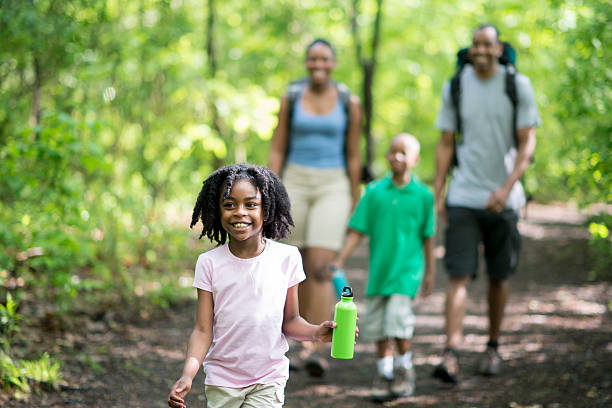 family hiking through the woods - bos spelen stockfoto's en -beelden