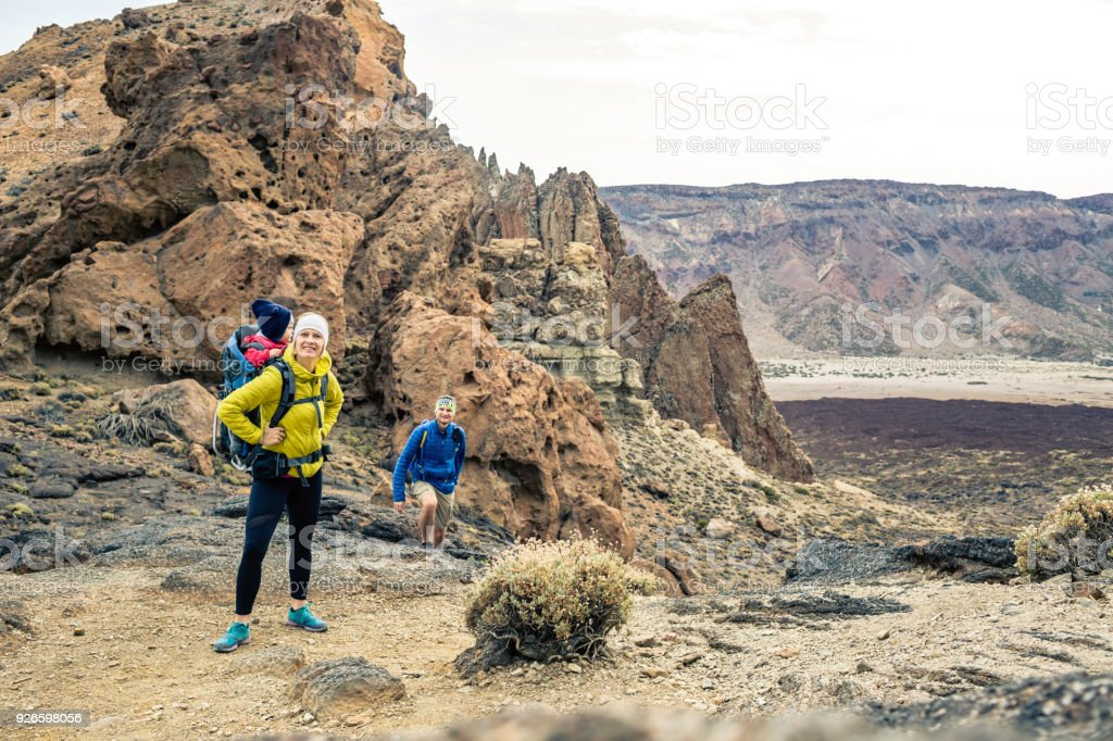 Family hiking with baby boy travelling in backpack stock photo