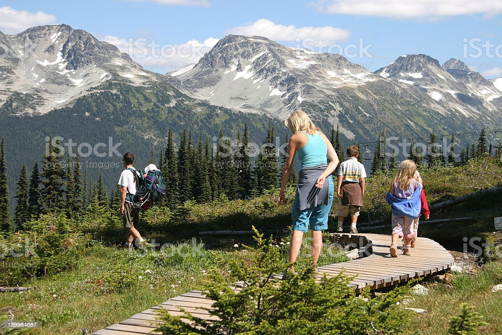 A family hiking with mountains in the background stock photo