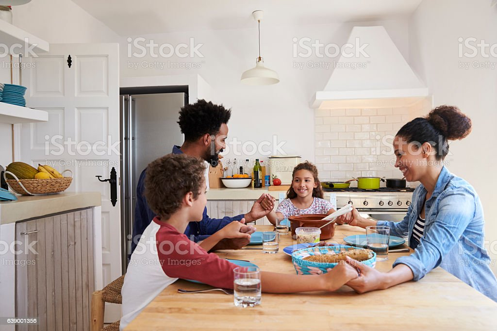 Family hold hands around the kitchen table before their meal stock photo
